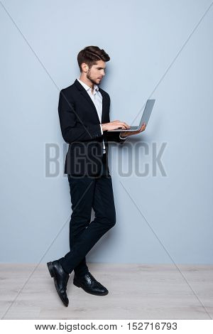 Full Photo Of Young Man In Black Suit Typing On Laptop