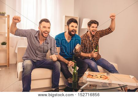 Portrait Of Three Happy  Men Holding Bottle Of Beer And Watching Tv