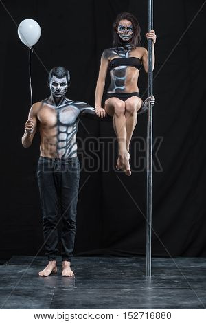 Athletic couple of pole dancers in the dark studio. Man holds a pylon with the left hand and holds a balloon in the right. Girl sits on the guy's left arm. They have a horrific body-art. Vertical.
