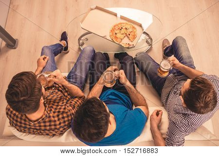 Top View Of Three Friends Sitting On Sofa With Beer And Pizza