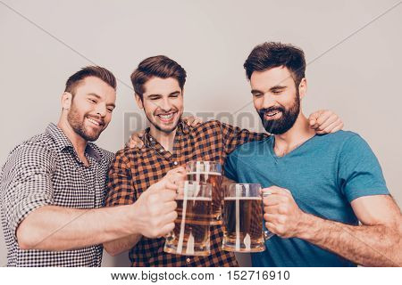 It Is A Goal! Three Happy Young Men Clinking With Glasses Of Beer