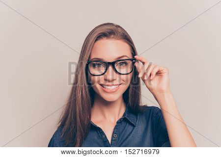 Young Teacher With Beaming Smile Touching Her Glasses
