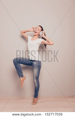Energetic Young Girl Listening Music In Headphones And Dancing