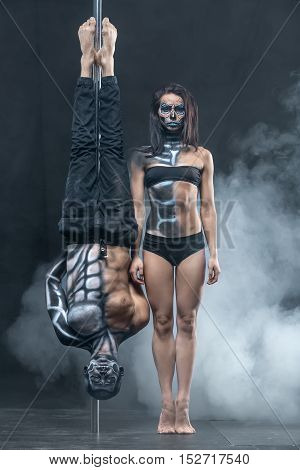 Incredible couple of pole dancers with a horrific body-art in the dark studio with a cloud of a smoke. Man hangs upside down on a pylon. Girl stands on her toes next to him. Vertical.