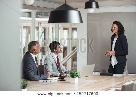 Young businesswoman standing in a boardroom giving a presentation to two work colleagues sitting a table