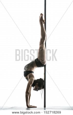 Sportive pole dancer with a body-art stands on the hands upside down in a studio on a white background. She uses a pylon like a fulcrum. Her legs are stretched. Girl wears black sport underwear. Vertical.