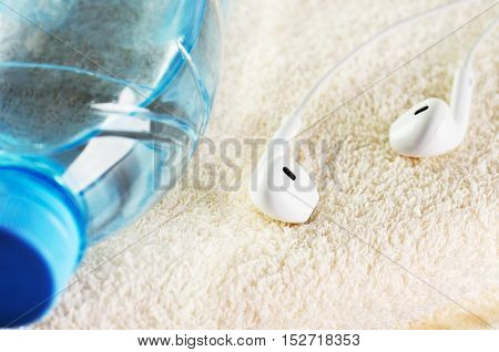 white headphones and a bottle of water close-up on a terry towel horizontal
