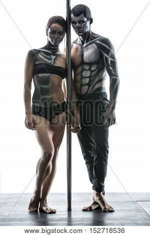 Attractive couple of pole dancers with horrific body-art stands next to a pylon in the studio on the white background. They are holding their hands together and looking into the camera. Vertical.