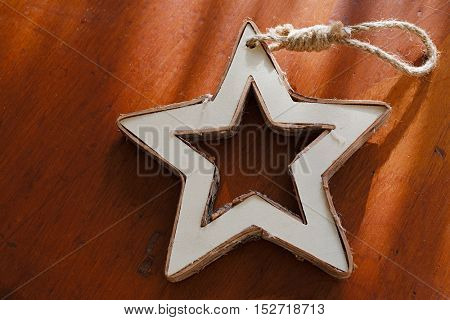 Wooden Christmas tree ornament in the shape of a star.