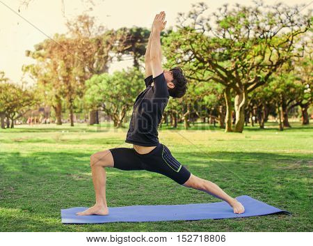 Young handsome latin man doing yoga in the park spring morning. Lifestyle.