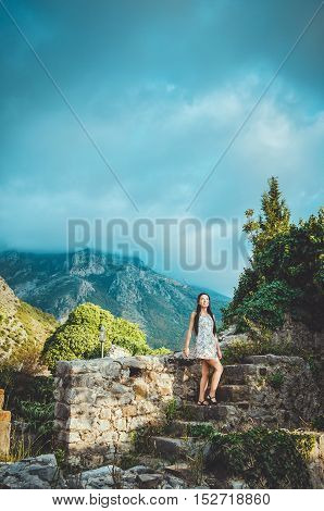 Feminine young romantic woman walking in Old Bar, Montenegro. Brunette female with long hair in dress posing on ancient ruins, mountains and blue cloudy sky. European summer vacation concept.