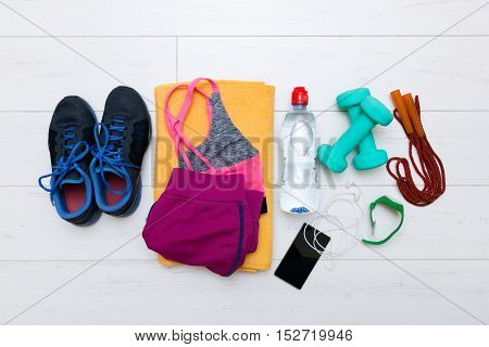 top view of fitness workout items on white gym floor