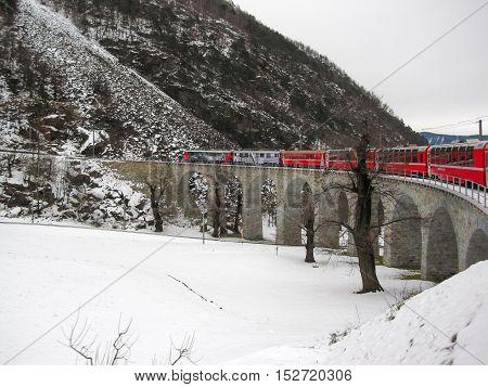 20 December 2012: The Bernina Express Crossing A Viaduct Bridge In Winter. The Bernina Express Is On