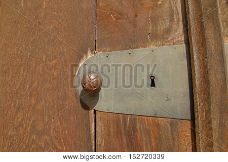 The picture was taken in Germany in the old town of Freising. The picture shows a part of an old door with the door handle. The handle is decorated with a cross.