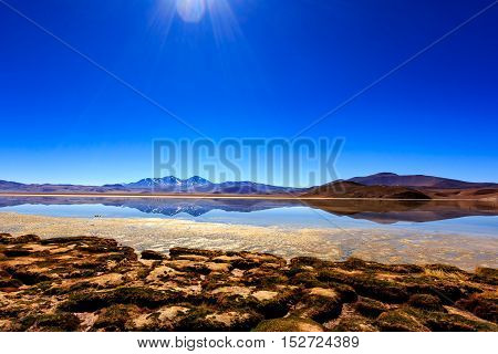 Snow covered mountains reflected on a salty lake at Atacama Desert