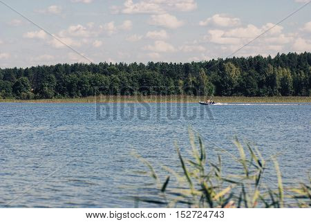 Lake and forest with running fishing boat at sunny day in Russia. Vacation.
