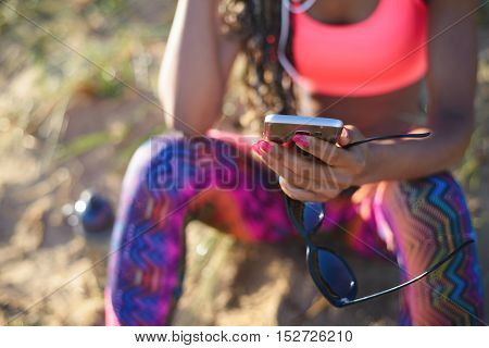 Sporty woman taking a workout rest for using her smartphone. Female hands holding cellphone and sunglasses. Summer fitness lifestyle and modern communication concept.