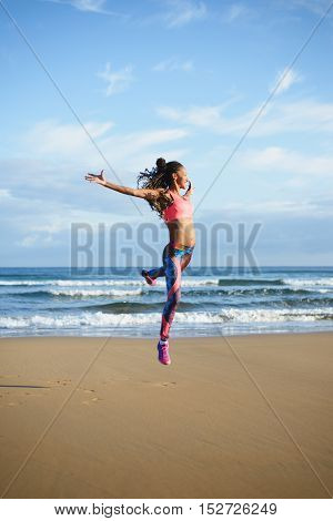 Sporty brazilian woman dancing and jumping at the beach. Black happy dancer practicing dance jumps and having fun outdoor.