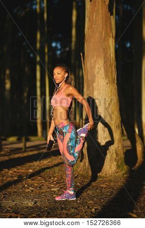Sporty black beautiful woman on fitness workout stretching legs for warming up before running. Brazilian girl in colorful fashion sportswear training in nature under sunrise light.