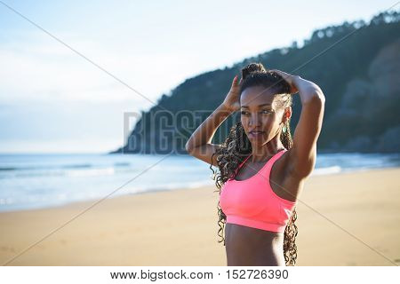 Woman getting ready for beach fitness workout. Black female athlete preparing for training outdoor on summer morning.