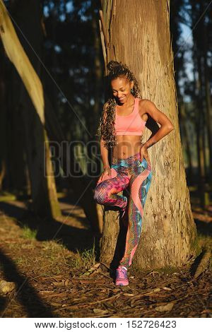 Fit sporty black sportswoman taking a fitness training rest leaning on a tree. Female athlete in colorful fashion sportswear.