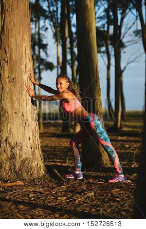 Sporty black beautiful woman on fitness workout stretching legs and calf for warming up before running. Brazilian girl in colorful fashion sportswear training in nature under sunrise light.