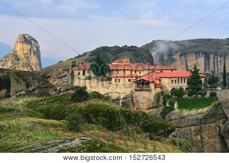 Meteora monasteries. Beautiful view on Monastery of the Holy Trinity placed on the edge of high rock illuminated of the first morning sun rays Kastraki Greece