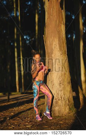Sporty black beautiful woman taking a fitness workout rest for playing music or texting on her smartphone. Brazilian girl in colorful fashion sportswear training in nature under sunrise light.