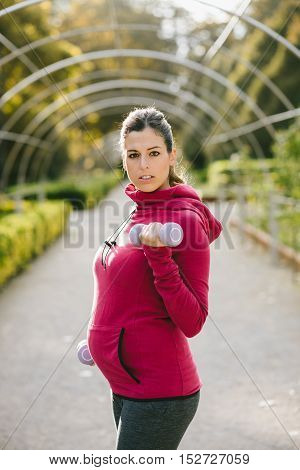 Fitness pregnant woman exercising with dumbbells. Gravid female athlete working out biceps outdoor at urban park on early autumn.
