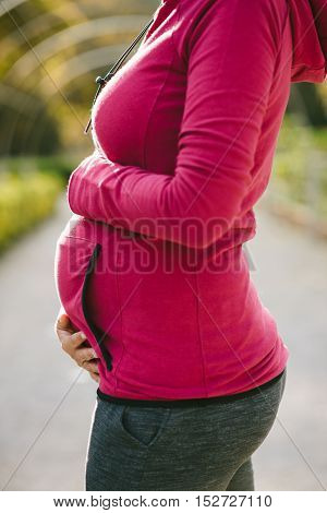 Pregnancy healthy and fitness lifestyle concept. Pregnant woman embracing her belly.