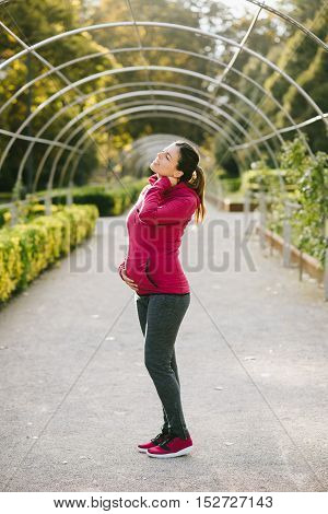 Pregnant fitness woman suffering from neck pain after training outdoor on early autumn park. Pregnancy pain and injury.