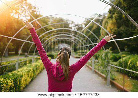 Back view of successful sporty woman raising arms. Female athlete doing victory gesture for celebrating workout goals and success.