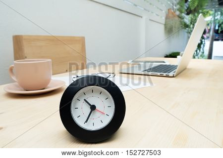 Wood table with black clock coffee cup laptop and resume information. business time concept.
