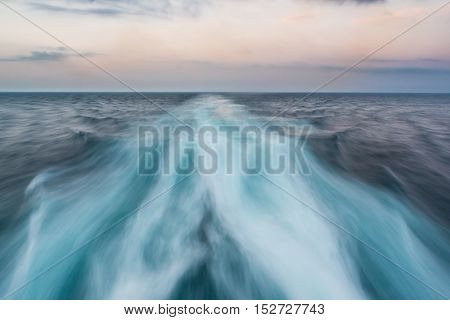 Looking at the sea from the back of a ferry. Motion blur of the moving water.