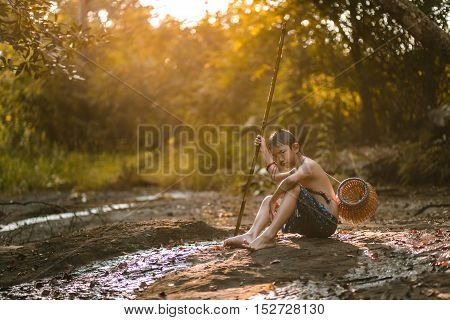 Boy fishing with spear in the countryside