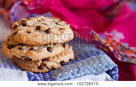 Oatmeal cookies with chocolate chips stacked on a white blue pink background. Selective focus