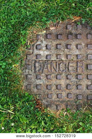 Old sewer manhole with the word danger on it with green grass around it alert sign background texture