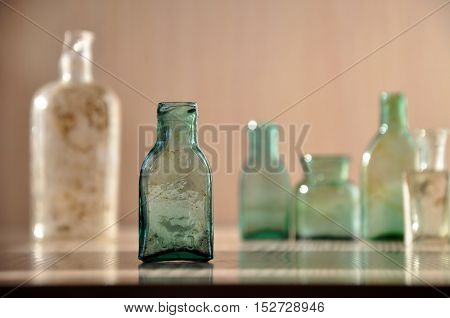 Little glass vintage green bottle closeup. Different glass bottles in the background.