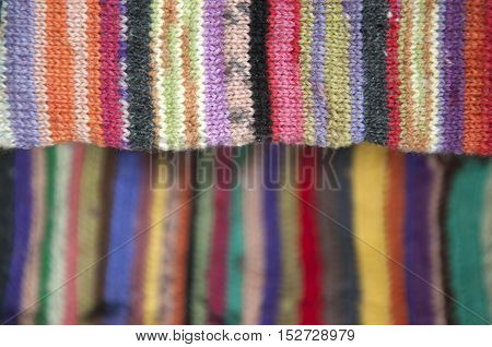 Striped colorful woolen knitted fabric closeup. Selective focus and blurred background.