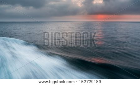 Looking at the sea from the back of a ferry at dawn. Motion blur creates movement.