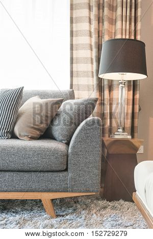 Row Of Pillows On Grey Sofa With Black Lamp In Living Room