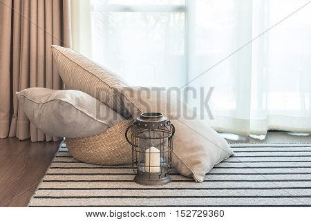Set Of Pillows On Carpet With Candel In Classic Black Lamp