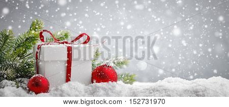 White gift box and christmas balls on snow