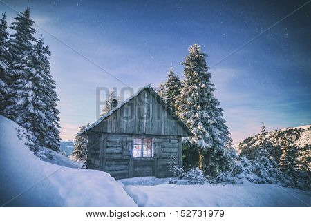 wooden house in winter forest, toned like Instagram filter