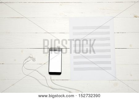 smart phone with music paper note on white wood background