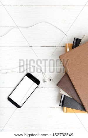 top view of stack of book with phone and earphone on white wood background