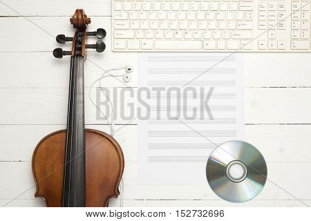 violin with keyboard computer music paper note and dvd disc on white wood background