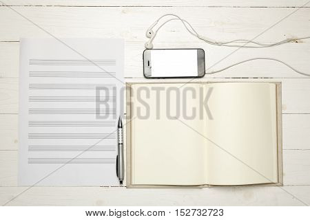 paper music note with smartphone on white wood background