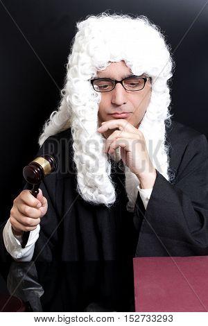 Portrait Of Male Lawyer with eyeglasses Holding Judge Gavel on black background