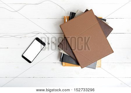 top view of stack of books with phone and earphones on white wood background
